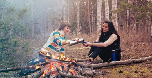 Two women sitting in front of burning firewood