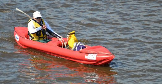 Man wearing a life vest was paddling the best inflatable kayak