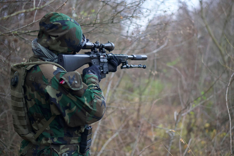 man using shooting gun with spotting scope