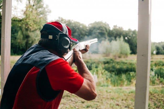 man shooting using shotgun and wearing earmuffs