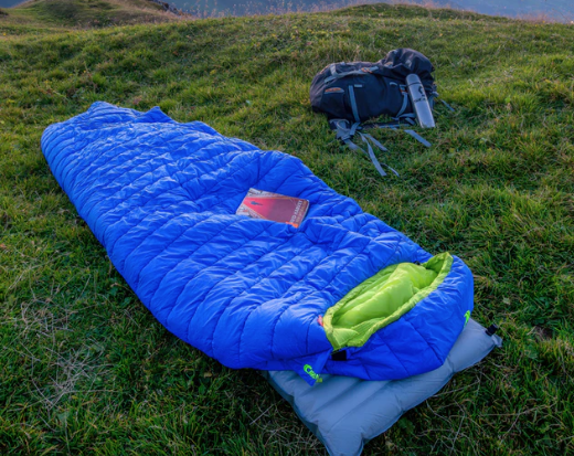 blue sleeping bag on grass