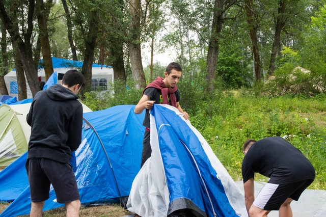three people pitching a tent