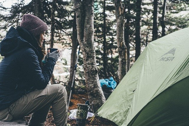 woman having coffee beside the tent