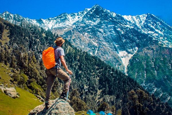 man-wearing-blue-shirt-standing-on-cliff-while-watching-mountain