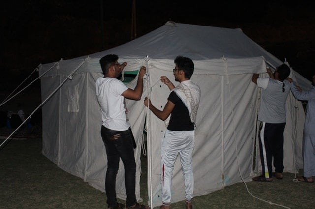 a group pitching the canopy tent