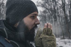 a man rubbing his hands due to cold weather
